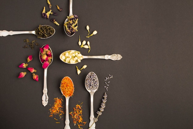 Draufsicht auf verschiedene teesorten in den silbernen löffeln auf der schwarzen oberfläche