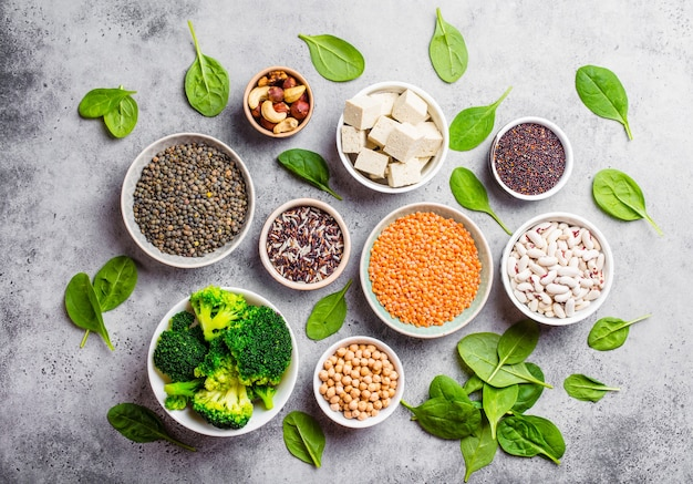 Draufsicht auf verschiedene vegane proteinquellen: bohnen, linsen, quinoa, tofu, gemüse, spinat, nüsse, kichererbsen, reis, rustikaler steinhintergrund. gesunde ausgewogene vegetarische ernährung für veganer