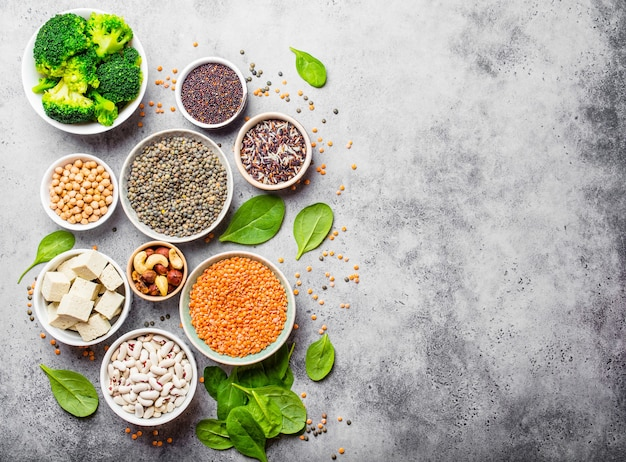 Draufsicht auf verschiedene vegane proteinquellen mit platz für text: bohnen, linsen, quinoa, tofu, gemüse, nüsse, kichererbsen, reis, steinhintergrund. gesunde ausgewogene vegetarische ernährung für veganer