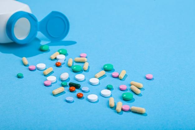 Draufsicht auf verschiedene von tablettenflasche verstreute bunte tabletten und kapseln auf blauer wand, nahrungsergänzungsmittel, vitamine der pharmazeutischen medizin, horizontal, kopierraum, flache lage
