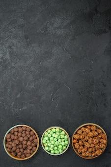 Draufsicht auf verschiedene zuckerbonbons in kleinen töpfen auf schwarz