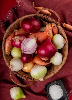 Draufsicht auf verschiedene zwiebeln im korb mit salz auf bordotuch und roter oberfläche