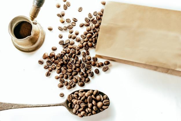 Draufsicht auf verstreute kaffeebohnen, eine papptüte, einen spon und eine rustikale kaffeemaschine rustic