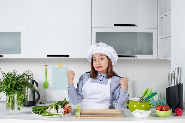 Draufsicht auf verwirrte köchin und frisches gemüse mit kochausrüstung und in der weißen küche
