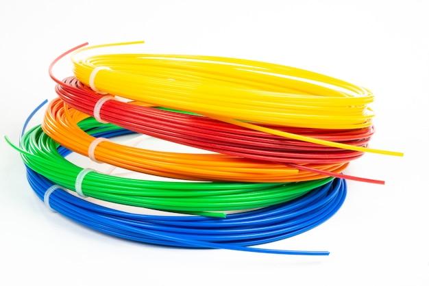 Draufsicht auf vier bunte gerollte filament-3d-stift-pla auf weiß