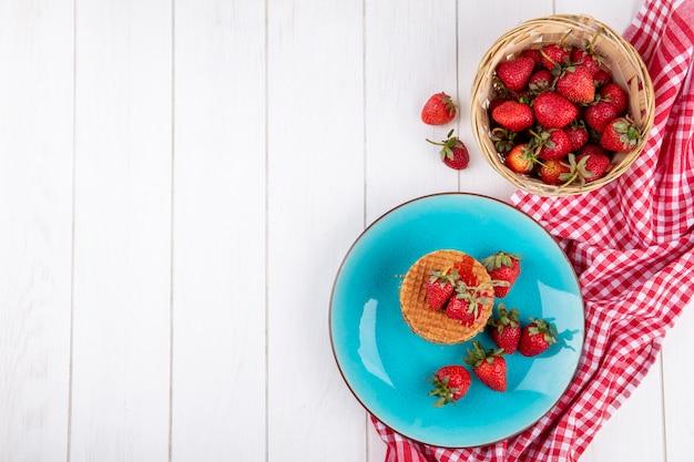 Draufsicht auf waffelkekse und erdbeeren im teller und im korb auf kariertem stoff und holzoberfläche