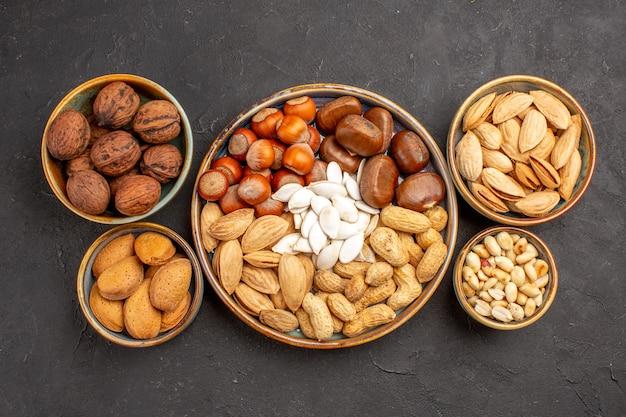 Draufsicht auf walnüsse, erdnüsse und andere nüsse auf dunkler oberfläche