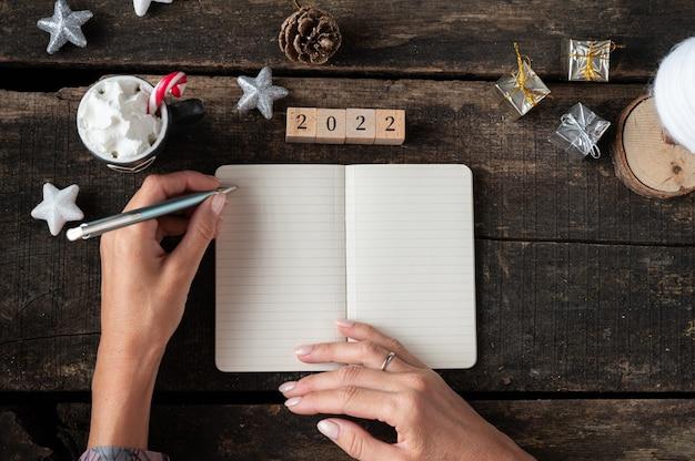 Draufsicht auf weibliche hände, die eine auflösung für das neue jahr 2022 und pläne in einem notizbuch auf einem weihnachtlich dekorierten holzschreibtisch schreiben