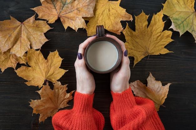 Draufsicht auf weibliche hände, die eine tasse kakao auf dem hintergrund des holztischs und der herbstblätter halten.
