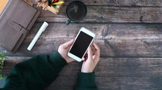 Draufsicht auf weibliche hände, die smartphone mit leerem bildschirm auf holztisch halten. leerer bildschirm für textnachrichten oder informationsinhalte.