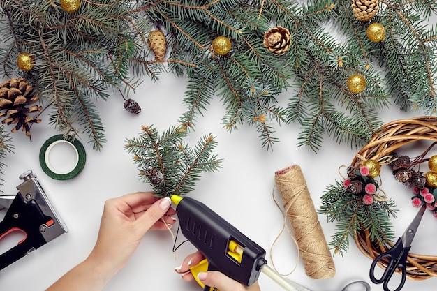 Draufsicht auf weibliche hände machen einen weihnachtskranz verpackte geschenke und schriftrollen fichtenzweige und werkzeuge ...