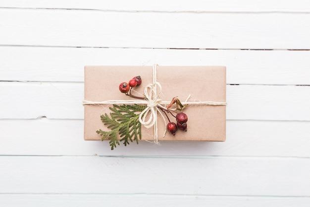 Draufsicht auf weihnachtsgeschenk in handwerk verpackt und mit verschiedenen natürlichen dingen auf weißem holz dekoriert decorated