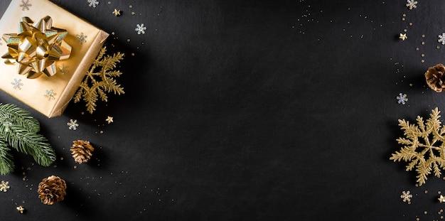 Draufsicht auf weihnachtsgeschenkbox, fichtenzweige, tannenzapfen und schneeflocke