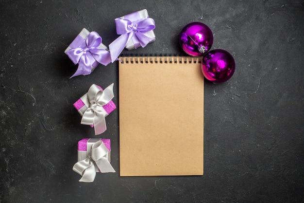 Draufsicht auf weihnachtsschmuck und notizbuch mit geschenken auf schwarzem hintergrund