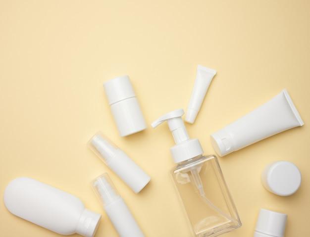 Draufsicht auf weiße cremetuben, kosmetikspender, leere gläser und mit handcreme, transparenter spender auf hellgelbem hintergrund. branding von kosmetikprodukten, mock-up