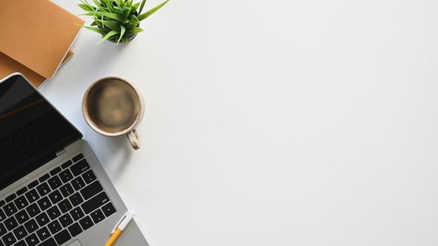 Draufsicht auf weißen schreibtisch mit zubehör computer-laptop, kaffeetasse, topfpflanze und notizbuch.