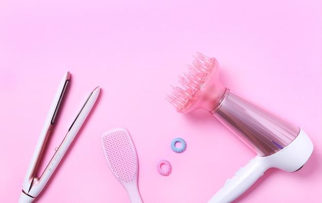 Draufsicht auf weißen und rosa fön, glätteisen, rosa haarbürste und zubehör auf rosa. flat lay, haarpflegekonzept. professionelles frisurenwerkzeug.