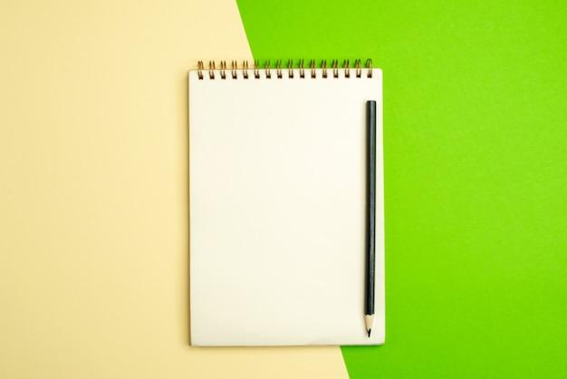 Draufsicht auf weißes notizbuch mit stift auf weißem und gelbem hintergrund