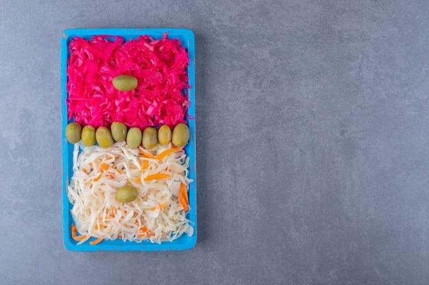 Draufsicht auf weißes und rosa sauerkraut mit oliven über blauem holztablett.