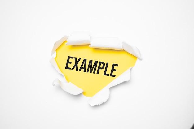 Draufsicht auf weißes, zerrissenes papier und den text beispiel auf einer gelben fläche