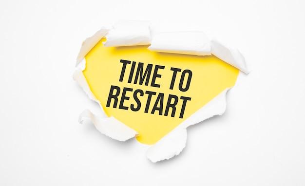Draufsicht auf weißes, zerrissenes papier und den text time to restart auf einer gelben oberfläche
