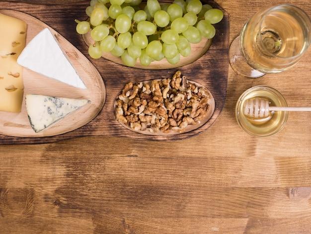Draufsicht auf weißwein, serviert mit honig auf holztisch. französischer käse. leckere trauben. köstlicher honig, kopienraum verfügbar.