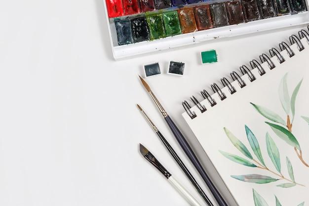 Draufsicht auf zeichnungen, pinsel, paletten- und aquarellfarben. arbeitsplatz des künstlers