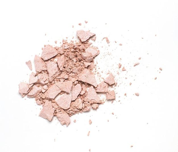 Draufsicht auf zerkleinertes rosa kompaktes hervorhebungspulver auf weißem hintergrund