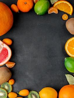 Draufsicht auf zitrusfrüchte als mandarinenlimette und andere auf schwarzer oberfläche