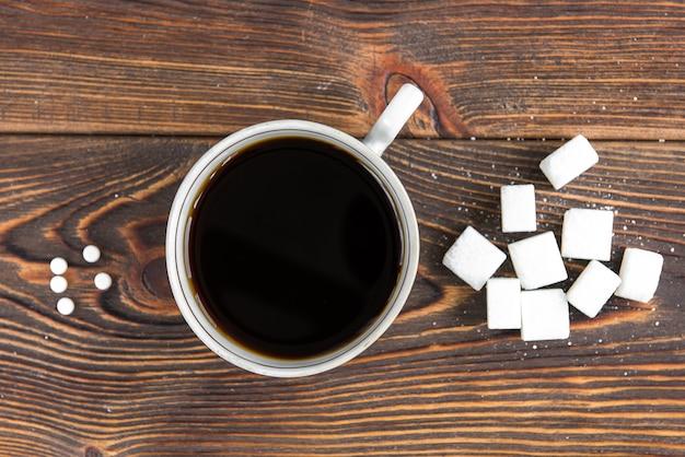 Draufsicht auf zucker und süßstoff mit einer tasse kaffee