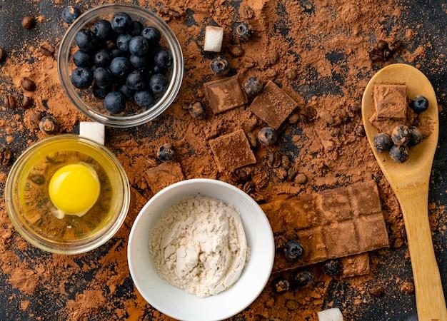 Draufsicht auf zutaten zum kochen oder backen von schokolade auf dem tisch, blaubeere, ei, mehl, kakao und pralinen