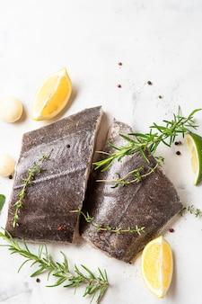Draufsicht auf zwei frische heilbutt-rohsteaks mit kräutern und zitrone auf weißem hintergrund. omega-3-fette. gehirnnahrung