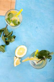 Draufsicht auf zwei gläser mit limonade auf blauem vintage-holzhintergrund