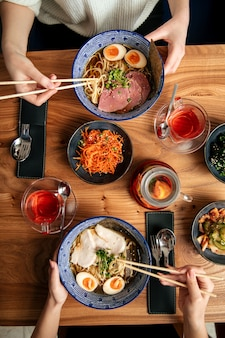 Draufsicht auf zwei leute essen japanische ramen-nudelsuppen und andere asiatische gerichte