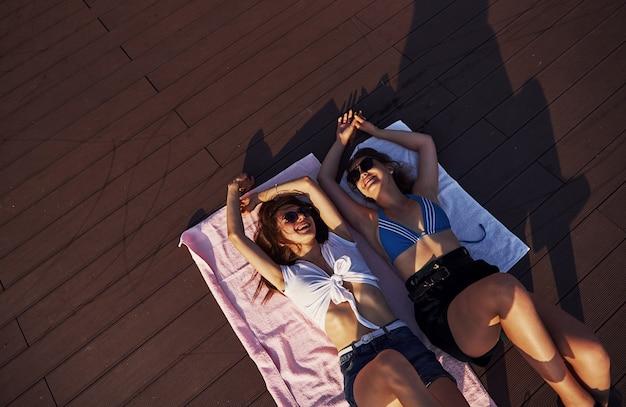 Draufsicht auf zwei mädchen am strand, die auf dem boden liegen und warmes sonnenlicht genießen.