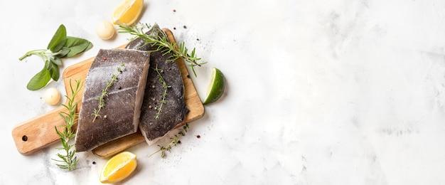 Draufsicht auf zwei rohe heilbutt-fischsteaks mit kräutern und zitrone auf holzbrett und weißem hintergrund. langes banner mit kopienraum. omega-3-fette sind gut für geistige klarheit. gehirnnahrung