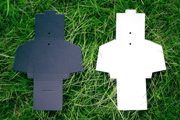 Draufsicht auf zwei schwarze und weiße leere aufgeklappte box für zubehör zum nähen von kleidungsetiketten auf grünem...