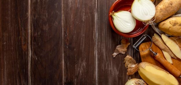 Draufsicht auf zwiebeln und geschälte kartoffeln