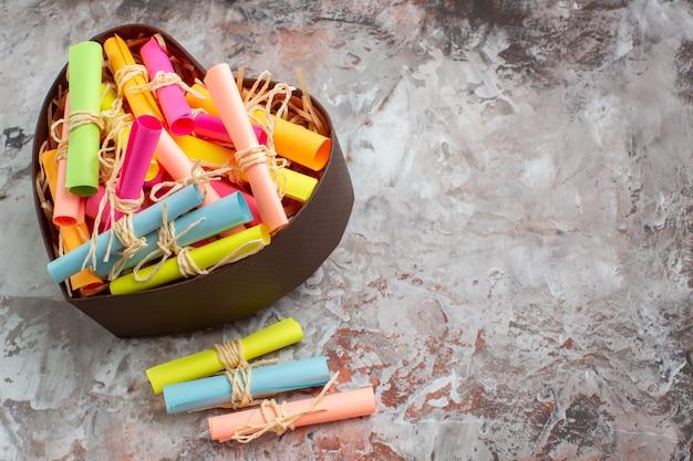 Draufsicht aufgerollte farbige haftnotizen in herzförmiger box auf braunem tisch mit freiem platz