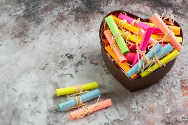 Draufsicht aufgerollte farbige haftnotizen in herzförmiger box auf braunem tischfreiraum