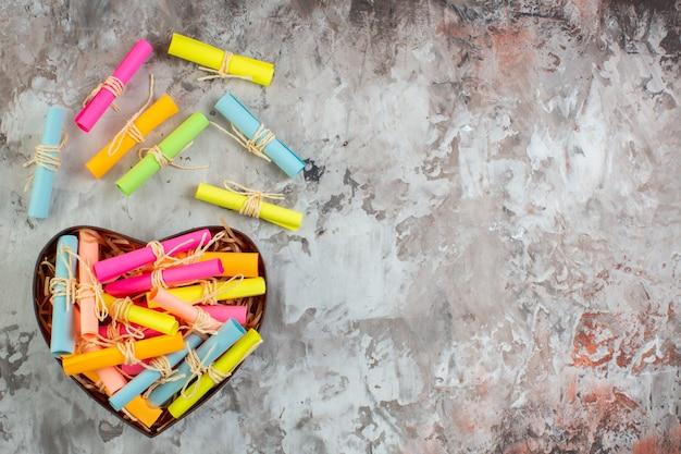 Draufsicht aufgerollte farbige haftnotizen in herzförmiger box auf dem tisch mit freiem platz