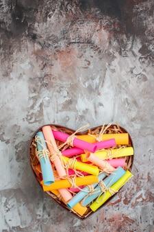 Draufsicht aufgerollte farbige haftnotizen in herzförmiger schachtel auf dem tisch