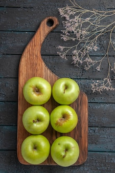 Draufsicht aus der ferne äpfel an bord sechs appetitliche grüne äpfel auf schneidebrett neben ästen auf dunkler oberfläche