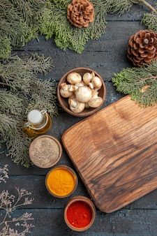 Draufsicht aus der ferne brett und gewürze holz braunes schneidebrett neben verschiedenen bunten gewürzen unter öl in flaschenzweigen mit zapfen und schüssel mit pilzen