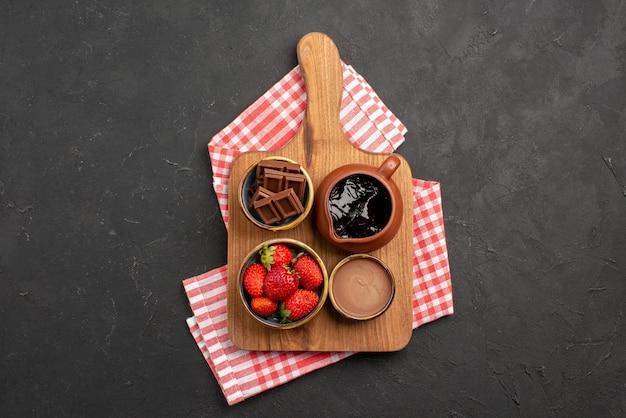 Draufsicht aus der ferne dessert auf tischdeckenschalen mit appetitlicher schokoladencreme und erdbeeren auf dem schneidebrett auf der rosa-weiß karierten tischdecke auf dem dunklen tisch