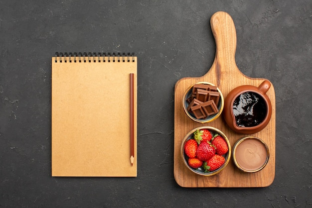 Draufsicht aus der ferne dessertschalen mit appetitlicher schokoladencreme und erdbeeren auf dem schneidebrett neben dem sahnenotizbuch und bleistift auf dem dunklen tisch