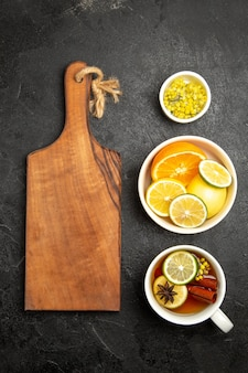 Draufsicht aus der ferne eine tasse tee holzschneidebrett neben den schalen mit kräutern und zitronenscheiben und einer tasse tee