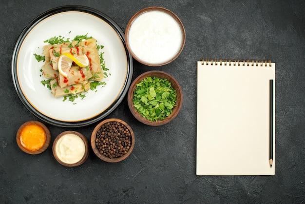 Draufsicht aus der ferne essen auf tischschüsseln mit sauerrahmkräutern, schwarzem pfeffer und gelber soße und gefülltem kohl mit kräuterzitrone und soße auf weißem teller neben weißem notizbuch und bleistift auf schwarzem tisch