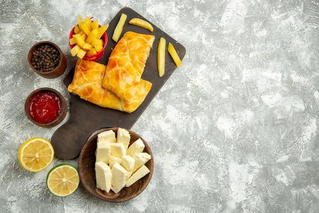 Draufsicht aus der ferne fastfood zwei kuchen und pommes frites auf dem brett neben den schüsseln mit käseketchup und schwarzer pfefferzitrone auf dem grauen tisch