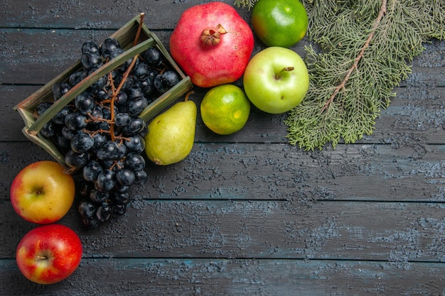 Draufsicht aus der ferne früchte auf tafeltrauben in holzkiste granatapfel birnen äpfel limetten neben fichtenzweigen auf dunklem tisch